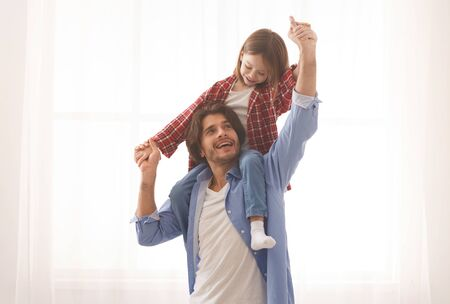 Cute little girl playing with her cheerful dad, sitting on his shoulders over white background, copy space