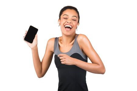 Fit Black Woman In Earbuds Listening To Music On Smartphone With Blank Screen Dancing Over White Background. Studio Shot
