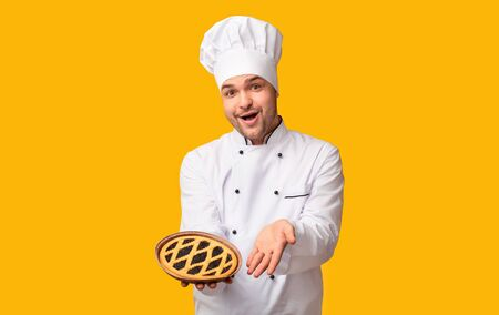 Easy Recipes. Positive Chef Baker Man Showing Pie Standing On Yellow Background. Studio Shot
