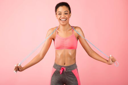 Fitness Concept. Happy African American Woman Holding Jump Rope Smiling Posing Over Pink Background. Studio Shot