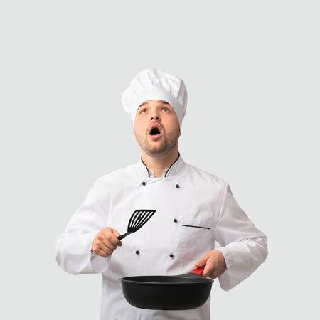 Essen zubereiten. Überraschter Koch Mann mit Pfanne und Spachtel nachschlagen stehend auf weißem Hintergrund. Studioaufnahme Standard-Bild