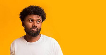 Dudoso joven negro mirando el espacio libre, sospechoso de lo que ve, panorama
