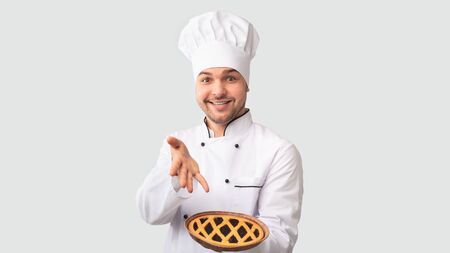 Cheerful Chef Man Showing Baked Pie Standing Over White Studio Background. Easy Culinary Recipes. Panorama Stockfoto
