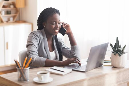 Busy Businesswoman Working At Desk In Office, Talking On Cellphone And Typing At Laptop, Copy Space