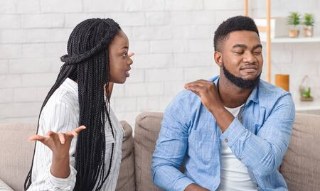 Family problems. Afro couple arguing at home, wife blaming husband while he is ignoring what she saying and showing bla bla bla gesture, panorama
