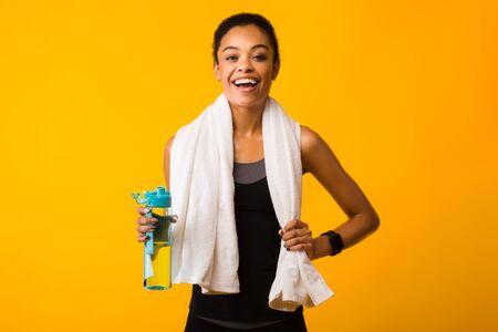 Fitness-Lifestyle. Fröhliche Afroamerikanerfrau, die eine Flasche Wasser hält und in die Kamera lächelt, die im Studio auf gelbem Hintergrund steht.