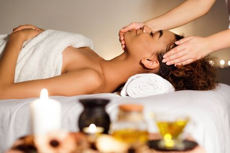 Afro girl receiving face massage with aroma composition nearby, relaxing in spa center, side view Фото со стока