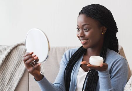 Skin Care Concept. Beautiful Black Woman Looking in Magnifying Mirror And Holding Face Cream Jar At Home
