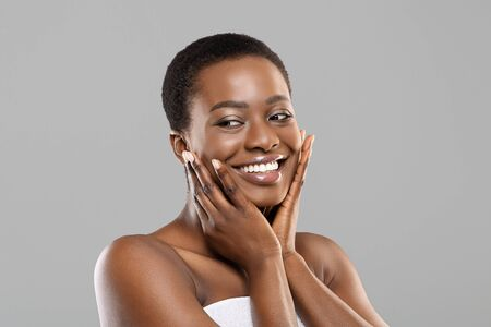 Face massage. Attractive african american woman touching her smooth flawless skin on cheeks, posing over gray background with copy space