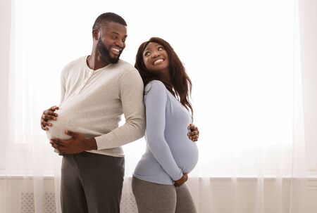 Support during pregnancy concept. Pregnant afro couple having fun at home, comparing size of their big belly, smiling man putting ball under shirt, free space