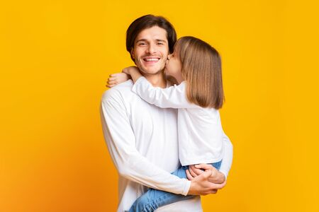 Preschool girl kissing smiling father over yellow studio background, fatherhood concept, copy space