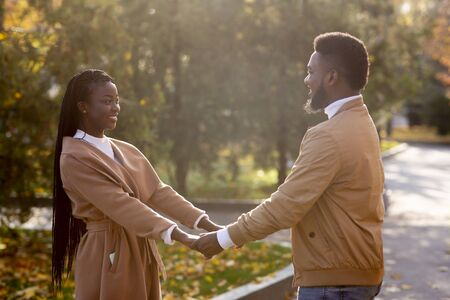 Young black couple in love holding hands while having date in autumn park, free space