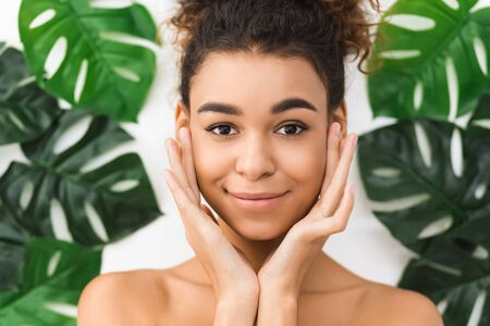 Cosmetology concept. African-american woman posing against tropical leaves and touching cheeks