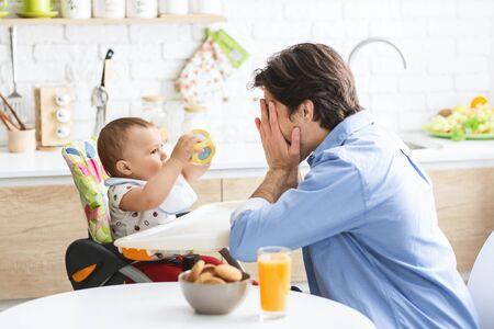 Coucou. Papa gai jouant avec le fils mignon de bébé dans l'intérieur de cuisine, espace vide