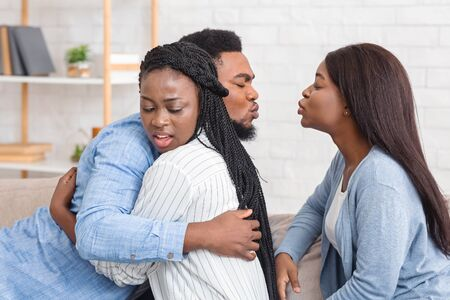Marital Infidelity And Love Triange Concept. Cheating Afro Man Kissing Another Woman While Hugging With His Wife On Couch At Home.