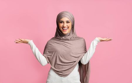 Cheerful muslim girl in hijab demonstrating something on her empty palms, comparing variants, making scales of her hands over pink background