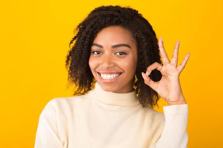 Everything Is Okay. Smiling curly black woman showing ok sign and looking at the camera over yellow background