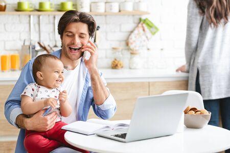Praca w weekendy. Wesoły tata konsultuje się z klientami telefonicznie, pracuje z uroczym synkiem w domowej kuchni, wolne miejsce