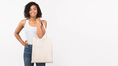 Zero Waste Concept. Black woman with eco tote bag over white studio background. Panorama, mockup, copy space