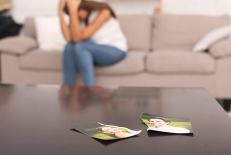 Unrecognizable Woman Crying After Breakup With Ex Boyfriend Sitting On Sofa Indoor, Torn Apart Photo Of Couple Lying On Table 写真素材