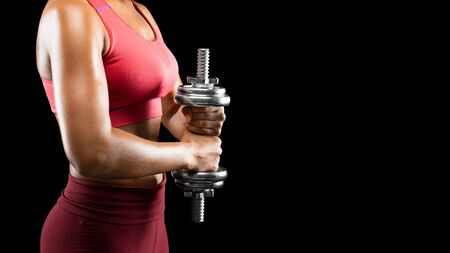 Side view of sporty african girl holding barbell over black background, making work out for shoulders, cropped, panorama with free space