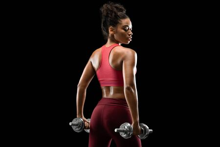 Back view of african female bodybuilder with barbells over black studio background, working out
