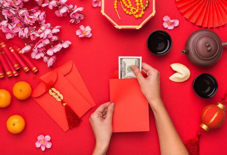 Woman preparing dollars for present on Chinese New Year, traditional decorations symbolising wealth Stock Photo
