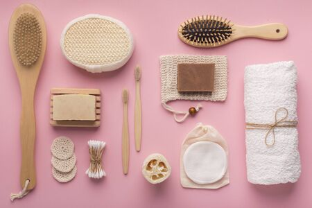 Creative flat lay of natural spa accessories with cocoa soap on pink background