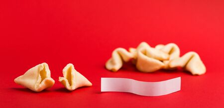 Traditional Chinese new year fortune cookies on red background with white paper for text, panorama, copy space