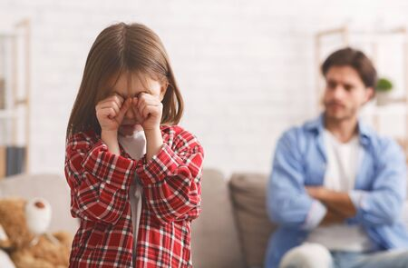 Quarrel With Father. Little girl crying, angry man sitting on sofa on background