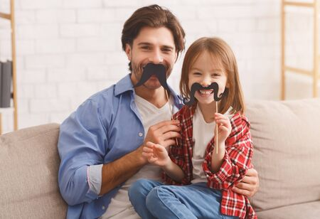 Beautiful funny little girl and daddy have mustaches on sticks, posing at home. Family holidays and togetherness concept, copy space