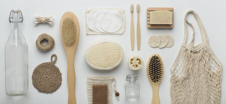 Eco friendly. Flat lay of bamboo brushes, eco soap, reusable net bag and glass bottle on white background, panorama