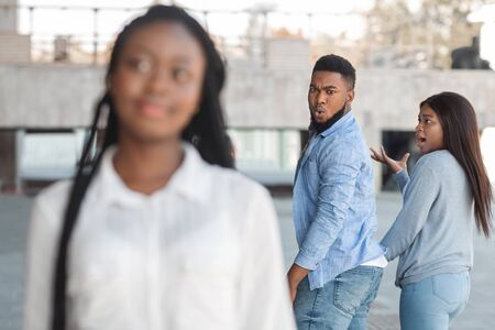 Distracted african american guy turning around and looking to another woman while walking with his girlfriend
