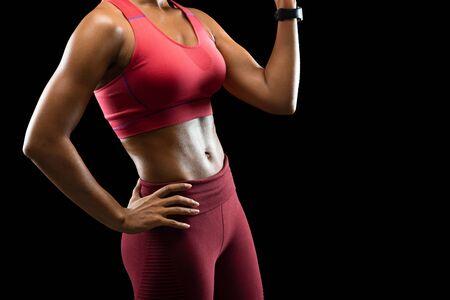 Athletischer Körper des afrikanischen weiblichen Fitnessmodells über schwarzem Hintergrund, beschnitten, freier Raum Standard-Bild