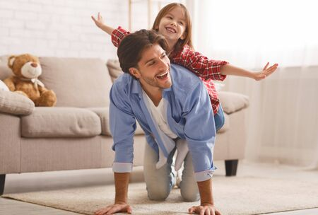 Happy childhood concept. Father and daughter spending weekend together at home, little girl riding fathers back, copy space Stock Photo