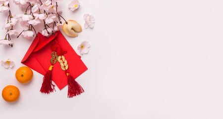 Chinese New Year festival concept. Sakura with mandarins and red envelopes with congratulations, white background, copy space, panorama