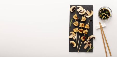 Healthy vegetarian tofu kebabs with grilled mushrooms, served with soy sauce and chopsticks in asian style, panorama with empty space