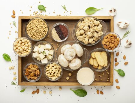 Vegan protein sources. Wooden tray with set of soybean products, nuts, legumes and mushrooms, top view
