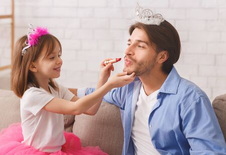 Cute little princess putting lipstick on her father. Young father enjoying time with child at home
