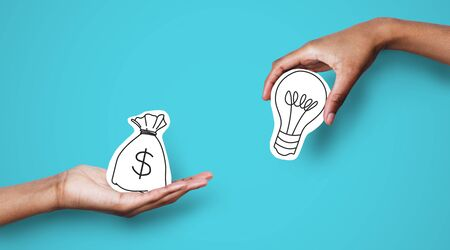 Startup supporting. Hands with dollar sign bag and light bulb over blue background, investor giving creator money