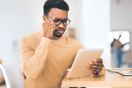 Reading News. Pensive black businessman in glasses using tablet checking his mail or schedule, free space Foto de archivo