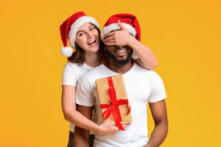 Cheerful young woman in santa hat surprising her black boyfriend with Cristmas gift, posing together over yellow studio background with free space