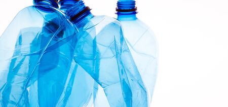 Mineral water bottles crushed and crumpled against white isolated background, panorama, copy space