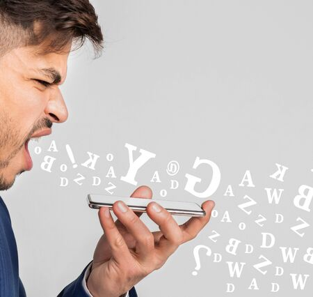 Angry businessman screaming at smartphone, having stressful conversation, diverse alphabet letters flying out of his mouth over light background Imagens