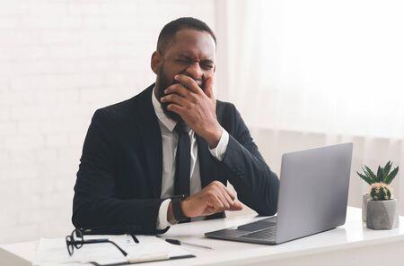 Tired young black businessman yawning at job, lack of motivation, copy space Reklamní fotografie