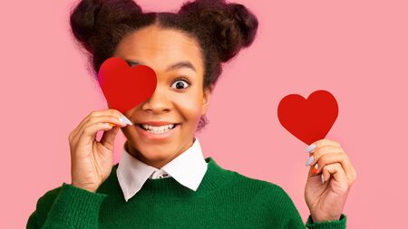Charity Concept. African american girl covering eye with paper heart over pink background. Panorama, empty space