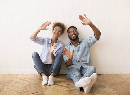 Relocation. Cheerful Black Couple Talking Planning Renovation And Interior Design Sitting On Floor After Moving In New House. Фото со стока