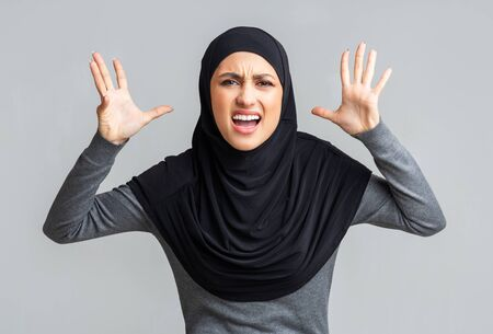 Enough. Stressed muslim woman in hijab screaming and emotionally gesturing over gray background, free space