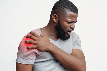Young afro guy suffering from shoulder pain injury, healthcare and medical concept