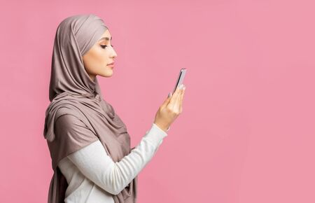 Profile portrait of serious muslim girl in hijab looking at smartphone in hands, reading message or using face recognition option to unblock device 版權商用圖片